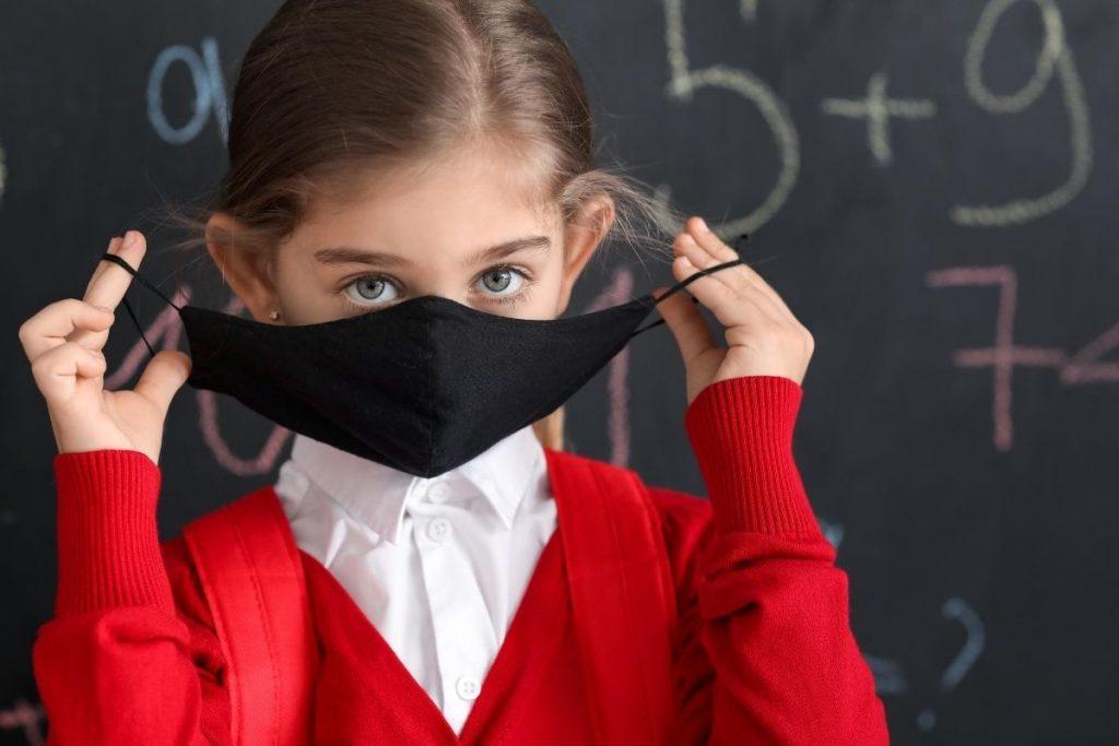 Bambina con mascherina davanti a lavagna